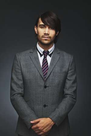 Portrait of handsome young businessman looking at camera. Asian male model in suite. Male executive posing against black background. photo