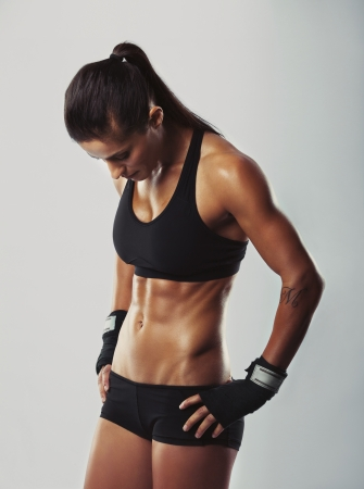 Image of muscular young female athlete wearing hand gloves standing looking down with her hands on hips on grey background. Woman bodybuilder resting after workout. Stock Photo