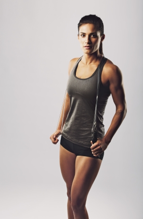 Portrait of attractive woman athlete holding jumping rope looking at camera against grey background. Female with muscular body posing. Health and fitness concept. photo