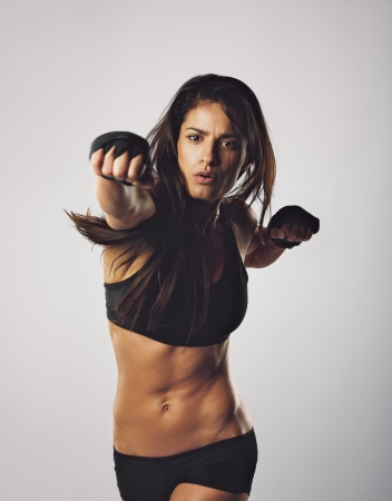 Young muscular woman practicing boxing. Middle eastern female throwing punch towards camera against grey background