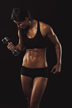 levantando pesas: Mujer sexy y en forma el levantamiento de pesas de mano. Femenina muscular que se resuelve con pesas en el fondo negro. Modelo Culturismo haciendo ejercicio físico.