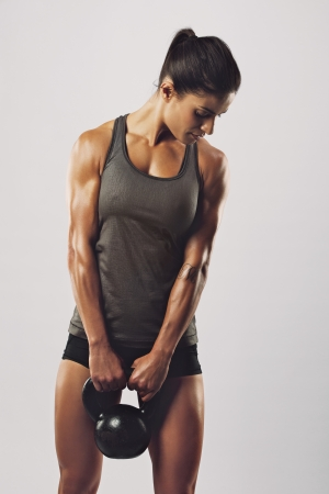 Fitness woman exercising crossfit holding kettle bell strength training biceps. Beautiful sweaty fitness instructor on grey background. Middle eastern female model with muscular fit and slim body. photo