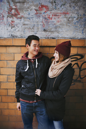 Happy young couple looking at each other against a wall. Teenage asian man and woman in love spending time together outdoors. photo