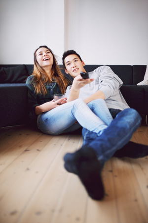 changing channels: Handsome young man holding remote control changing channels sitting with his beautiful girlfriend laughing while watching television. Happy teenage couple relaxing together at home watching TV.