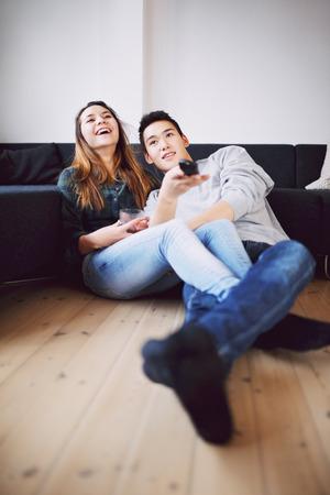personas viendo television: Hombre joven hermoso que sostiene el control remoto se cambian los canales que se sienta con su bella novia riendo mientras ve la televisión. Pares adolescentes felices juntos en casa viendo la televisión.