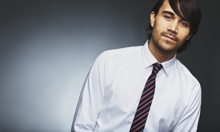Image of young male model in formal wear looking at camera. Mixed race businessman posing against grey with lots of copyspace.