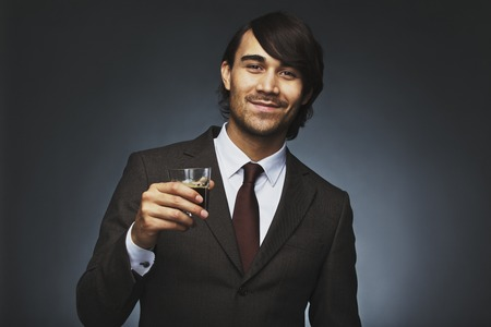 mixed race ethnicity: Portrait of successful young businessman holding a cup of coffee. Handsome male model in business suit with coffee posing against black .