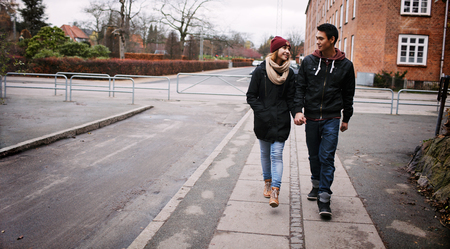 Young couple walking on a sidewalk holding hands looking at each other on a winter day. Asian teenage man and woman walking by a street. photo