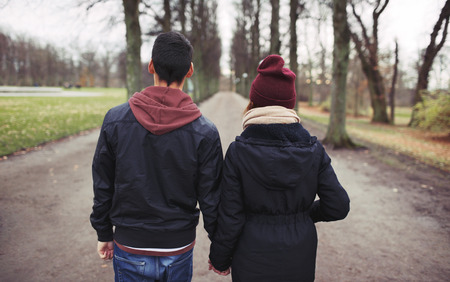 Rear view of teenage couple walking in park holding hands. Young man and woman in warm clothes outdoors. photo