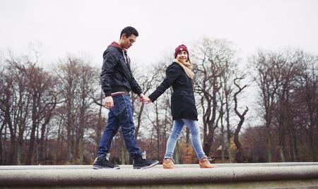pareja de adolescentes: Ángulo de visión baja del hombre joven y guapo con su novia caminando juntos tomados de la mano en el parque. Raza mixta pareja de adolescentes enamorados.