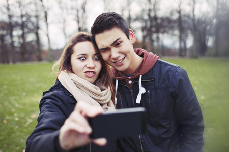 Funny teenage couple photographing themselves with smart phone in the park.