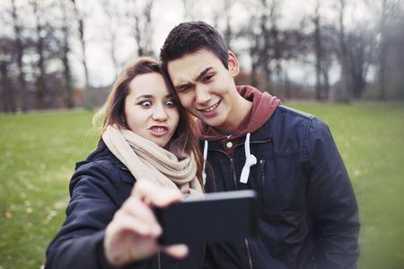 haciendo el amor: Pareja adolescente divertida que se fotografían con el teléfono inteligente en el parque. Foto de archivo