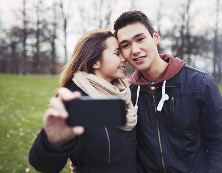 Affectionate young couple taking pictures using a smart phone at the park. Teenage boy and girl in love photographing themselves outdoors. photo