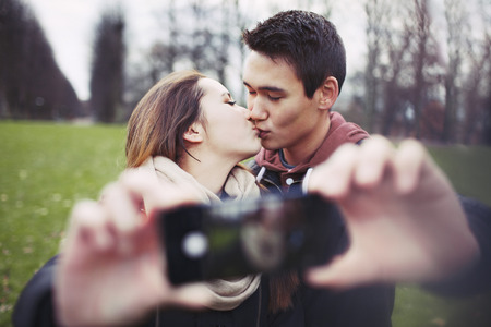 Lovely young couple taking self portrait while kissing at the park.  photo