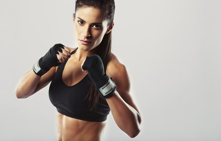 female boxing: Pretty young woman wearing boxing gloves posing in combat stance looking at camera. Fit young female boxer ready for fight on grey background