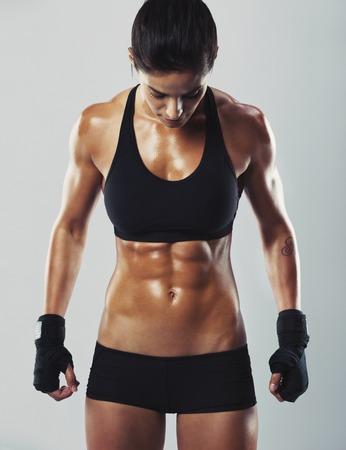 Retrato de una atractiva mujer de raza mixta, con cuerpo musculoso mirando hacia abajo mientras está de pie sobre fondo gris. Montar y sexy joven posando bodybuilder femenino. Foto de archivo