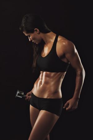 強いと筋肉の女性のボディービルのトレーニングの重みを持つ。フィットネスとボディービルのモデル。セクシーな女性は、黒の背景上のダンベル
