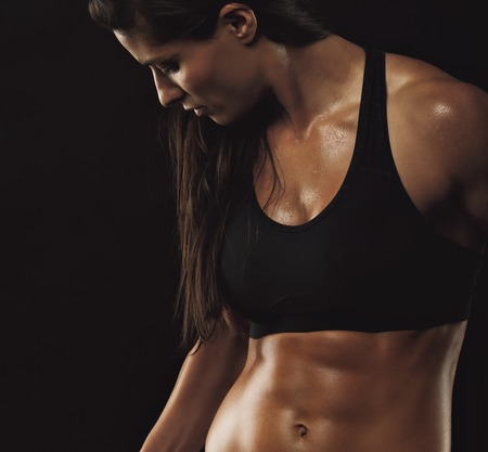 woman black background: Image of fitness woman in sports clothing working out on black background. Young female with perfect muscular body.