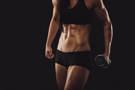 Bijgesneden afbeelding van sterk en gespierd vrouw te oefenen met gewichten. Vrouwelijke fitness vrouw op zwarte achtergrond Stockfoto