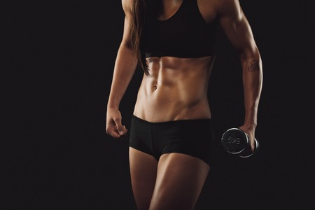 cropped image: Cropped image of strong and muscular build woman exercising with weights. Female fitness woman on black background