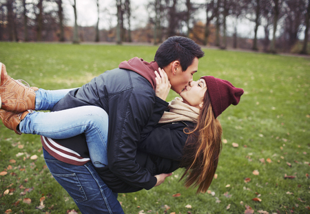 kissing couple: Attractive young man carrying his pretty girlfriend and kissing. Mixed race couple in love outdoors in park. Stock Photo