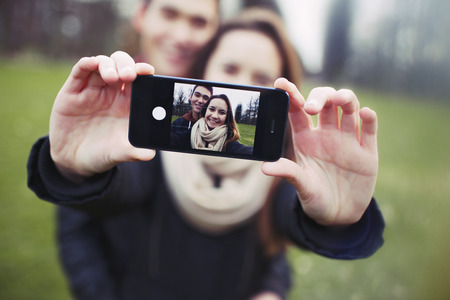 Affectionate young couple taking a self-portrait with a smartphone at the park. Mixed race teenage man and woman outdoors taking their picture with mobile phone. photo