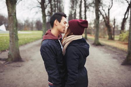 야외 공원에서 키스 사랑하는 젊은 부부. 혼합 된 경주 남자와 여자. 대 사랑. 스톡 콘텐츠