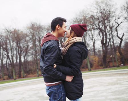besos apasionados: Raza mixta pareja de adolescentes a punto de tener un apasionado beso en el parque. Apuesto joven y bella mujer en ropa de abrigo juntos.