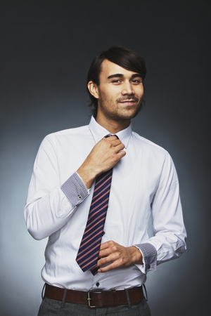 getting ready: Smart young businessman adjusting his necktie looking at camera smiling. Mixed race male model getting ready for office against black