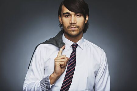 Portrait of attractive young businessman holding his coat over shoulder. Relaxed business executive against grey . Mixed race male model in formal attire. photo