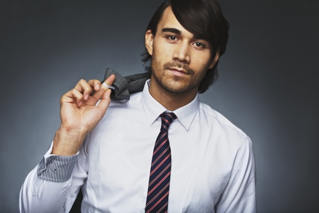 Portrait of attractive young man in formal clothing posing against grey . Young businessman holding his jacket over his shoulder. Mixed race male model looking at camera. photo