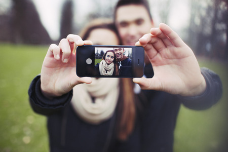 Mixed race young boy and girl making a funny face while taking a self portrait with mobile phone. Cute young couple photographing themselves with smartphone. Stock Photo