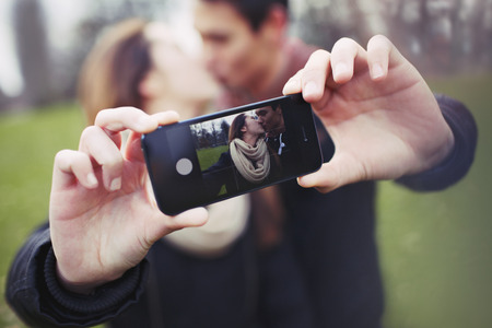 Loving young couple photographing themselves with a mobile phone while kissing at the park. Focus on smart phone. photo