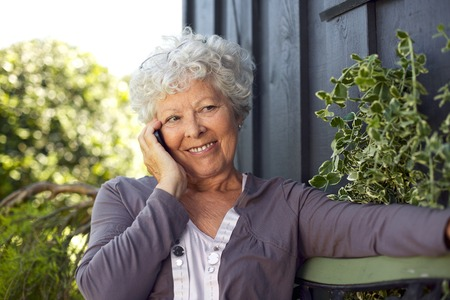 Happy elderly woman sitting on a bench in backyard talking on mobile phone and smiling photo