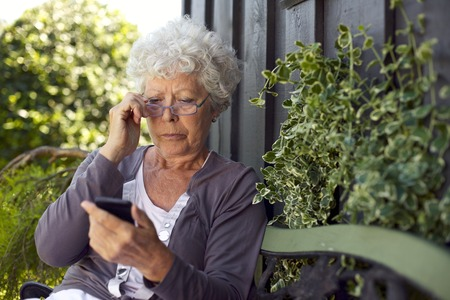 Senior lady sitting on a bench with her reading glasses in her backyard reading text message on her mobile phone