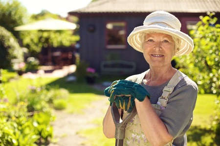 Portrait of senior woman wearing hat with gardening tools outdoors. Elder woman standing with shovel in her backyard garden photo