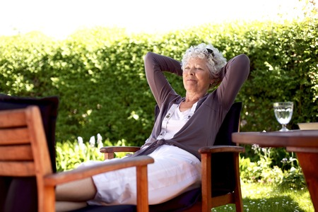 Senior woman sitting on a chair and taking a nap in backyard. Elder woman sleeping in backyard garden photo