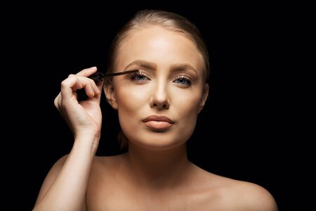 Closeup portrait of attractive young woman putting some mascara onto her eyelashes with make up brush. Beautiful caucasian female model against black background. photo