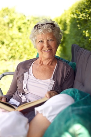 Happy old lady sitting in backyard garden holding a book and looking at camera smiling photo