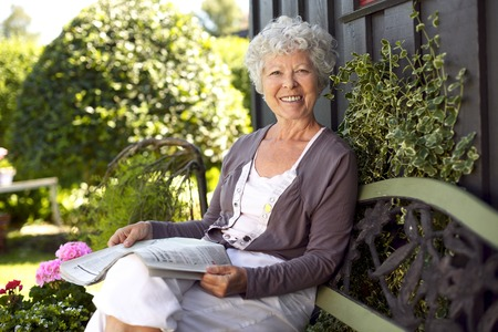 Happy senior woman sitting on bench in her backyard garden with a newspaper looking at camera smiling photo
