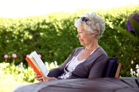 relaxed elder woman sitting in her backyard reading a book photo