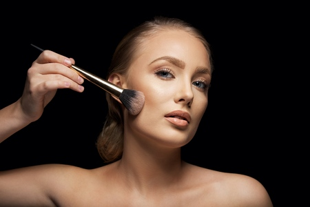 Attractive young woman applying foundation on her face with a make up brush against black background