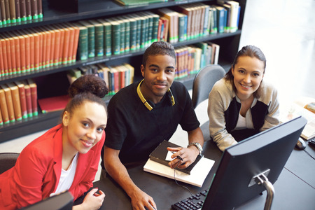 study table: Diverse group of young students working on computer in a public library Stock Photo