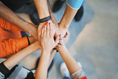together concept: Grupo multi�tnico de la gente joven poniendo sus manos en la parte superior de uno al otro