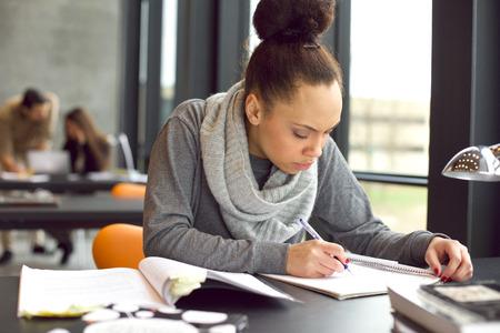 그녀의 연구를 위해 책에서 노트를 복용하는 여성 학생. 젊은 아프리카 계 미국인 여자 테이블에 앉아 책을 찾는 정보. 스톡 콘텐츠 - 27147545