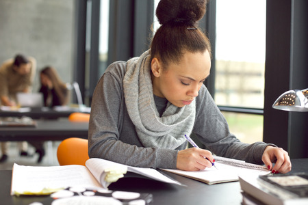 escribiendo: Mujer estudiante tomando notas de libros para su estudio. Mujer afroamericana joven sentado a la mesa con los libros para encontrar información.