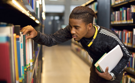 Young student finding reference books in university library. Finding information for his studies. photo