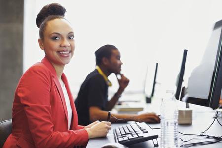 tabla de surf: American mujer feliz joven africano sentado frente a la computadora sonriendo a la cámara. Jóvenes estudiantes sentados en la mesa el uso de computadoras en la escuela.