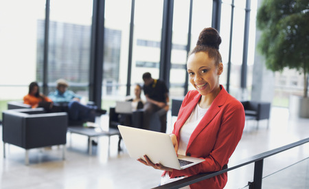 Beautiful young woman with a laptop in modern office. African american businesswoman standing by a railing with people working in background.
