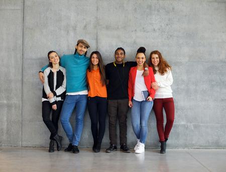 Skupina stylové mladých univerzitních studentů na akademické půdě. Mnohonárodnostní mladí lidé stáli proti zdi ve škole.